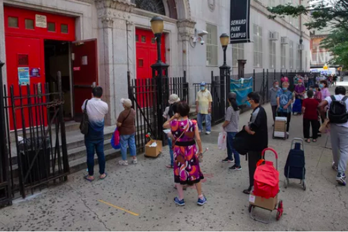 People pick up lunches outside a school building on the Lower East Side.
