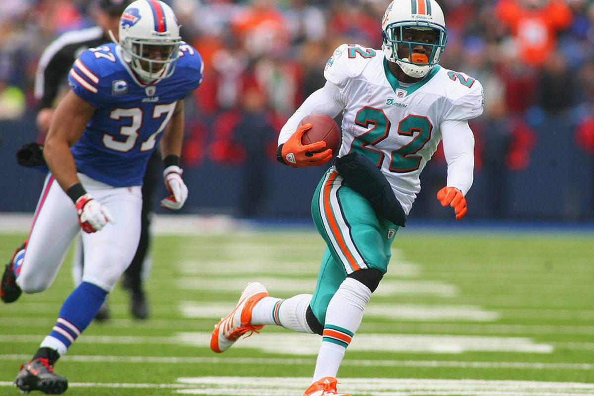 ORCHARD PARK, NY - DECEMBER 18:  Reggie Bush #22 of the Miami Dolphins runs against George Wilson #37 of the Buffalo Bills at Ralph Wilson Stadium on December 18, 2011 in Orchard Park, New York.  (Photo by Rick Stewart/Getty Images)