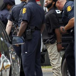 Pittsburgh police take Klein Michael Thaxton into custody after he held a businessman hostage at gunpoint inside a downtown Pittsburgh office building for more than five hours Friday, Sept. 21, 2012. Thaxton, 22, posted Facebook updates during the standoff, then surrendered to authorities without incident, police said. The man he took hostage was unhurt.