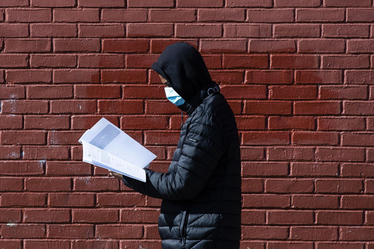 A high school student in Philadelphia, wearing a protective face mask, looks at a learning guide he picked up. Districts across the country are planning for remote learning due to the coronavirus pandemic.