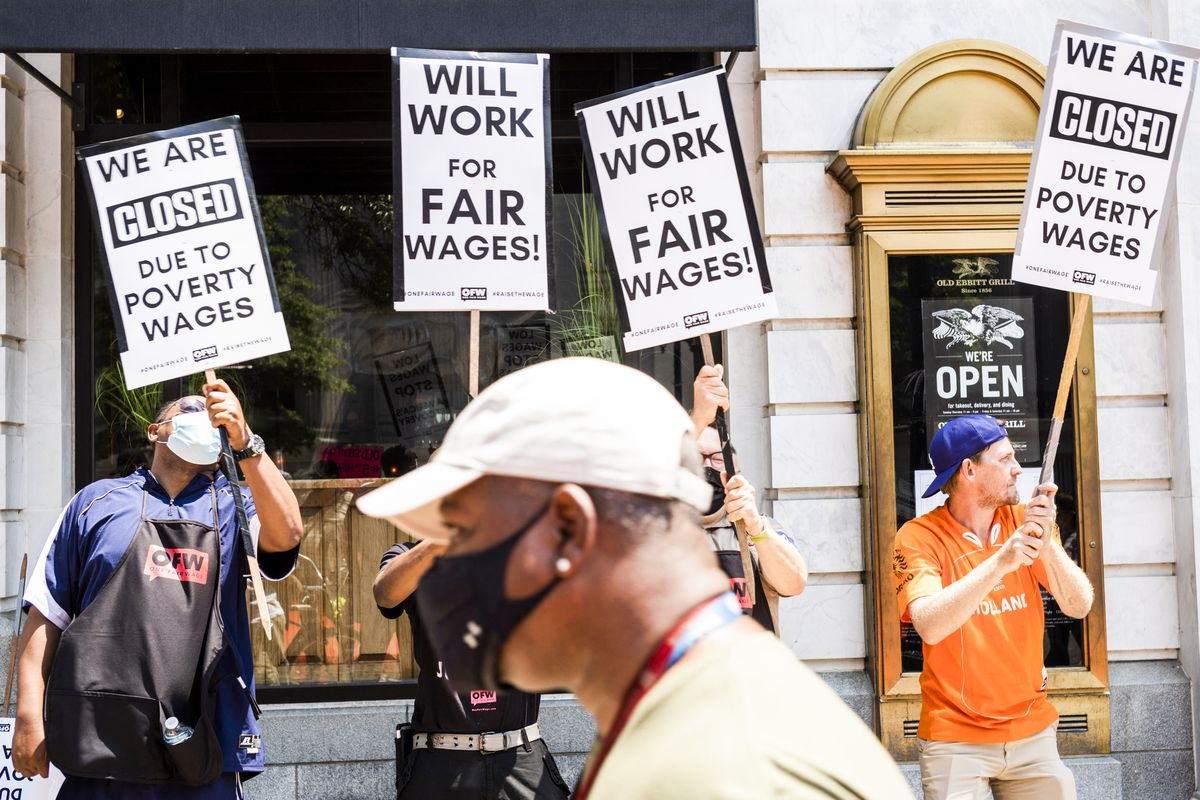 """Protesters outside a restaurant hold signs that read, """"We are closed due to poverty wages,"""" and, """"Will work for fair wages!"""""""