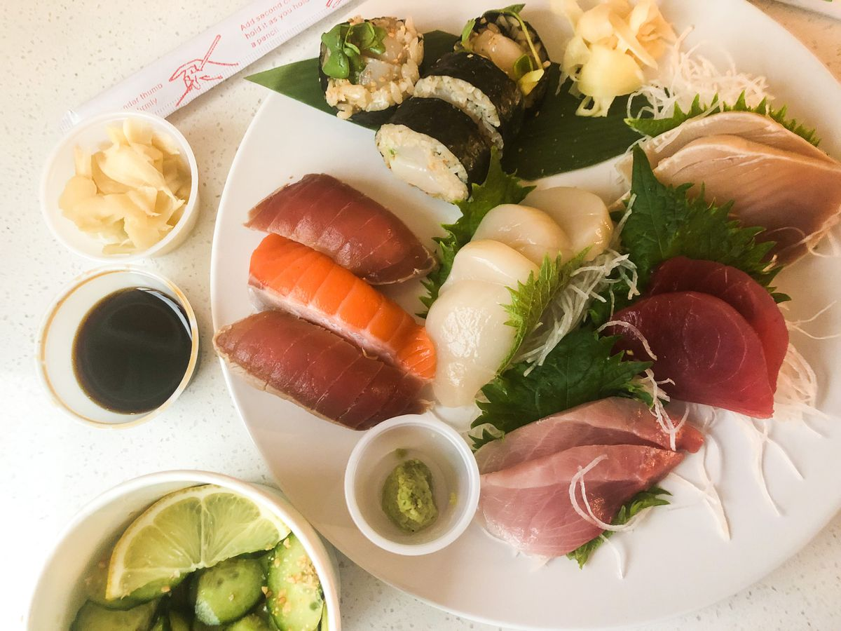 A white plate comes covered in tuna and salmon nigiri, scallop and yellowtail sashimi, and a yuzu scallop roll.