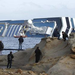 FILE - In this, Sunday, Jan. 22, 2012 file photo, people stop and look at the grounded cruise ship Costa Concordia off the Tuscan island of Giglio, Italy. Costa Crociere SpA says work to remove the capsized Costa Concordia cruise ship from its rocky perch off Tuscany will begin early next month and is expected to take 12 months. Costa said in a statement Saturday, April 21, 2012, the U.S.-owned company Titan Salvage won the bid to remove the ship, which struck rocks off the tourist-dependent island of Giglio on Jan. 13, when the captain made an unauthorized maneuver too close to shore.