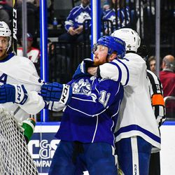 Syracuse Crunch Erik Condra (11) gets held out of a scrum by Toronto Marlies Travis Dermott (8) in American Hockey League (AHL) Calder Cup Playoff action at the War Memorial Arena in Syracuse, New York on Sunday, May 6, 2018. Toronto won 7-1.