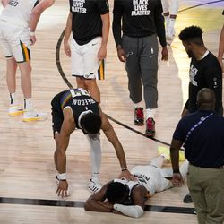 Denver Nuggets' Jamal Murray, center left, reaches down to console Utah Jazz's Donovan Mitchell (45), on floor, after the Nuggets 80-78 win during an NBA first round playoff basketball game, Tuesday, Sept. 1, 2020, in Lake Buena Vista, Fla.