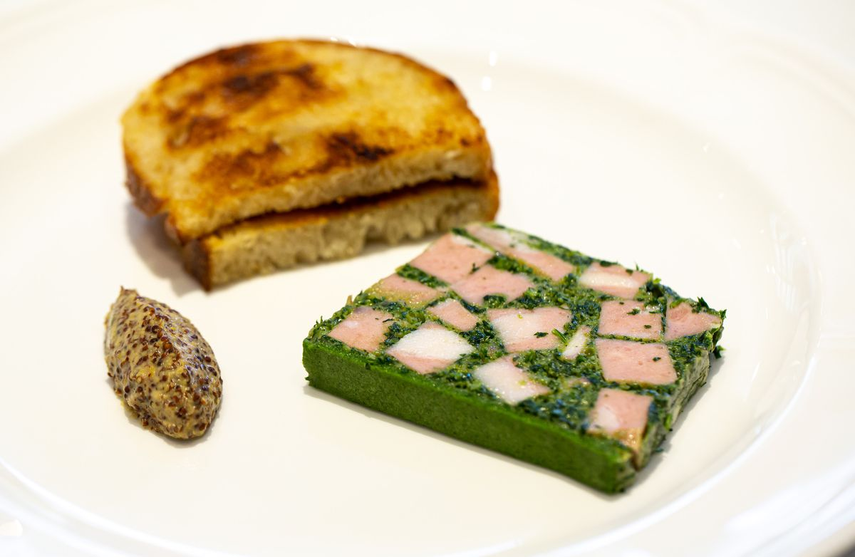 A terrine of foie gras with two pieces of toast and a dollop of dijon mustard