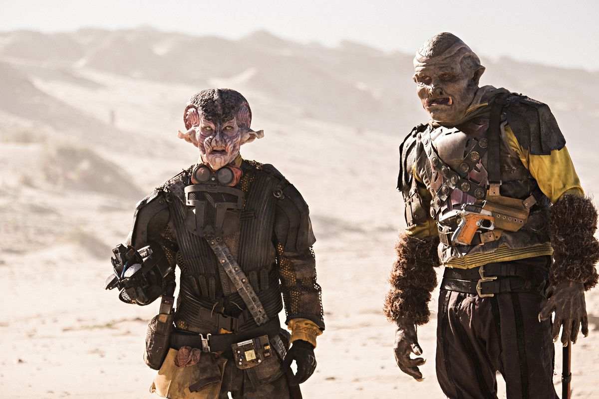 Two gnarly-looking aliens in grubby brown outfits covered with leather straps and worn-looking belts and bandoliers stand in the desert.