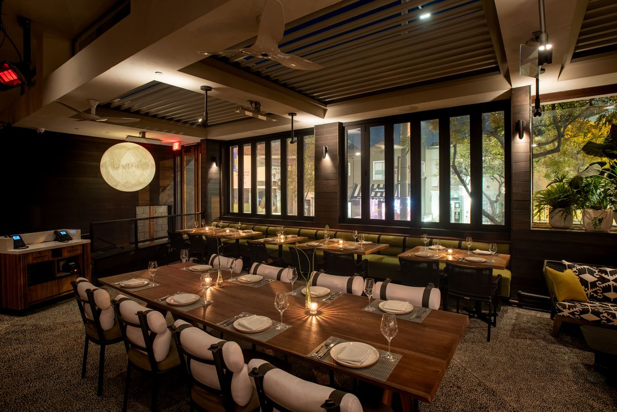 A large communal table with outdoor seats at a new restaurant, at night.