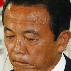 Japanese Prime Minister Taro Aso, leader of the Liberal Democratic Party, reacts as he looks at the report on the results of parliamentary elections during the ballot counting at the party headquarters in Tokyo, Japan, Sunday.