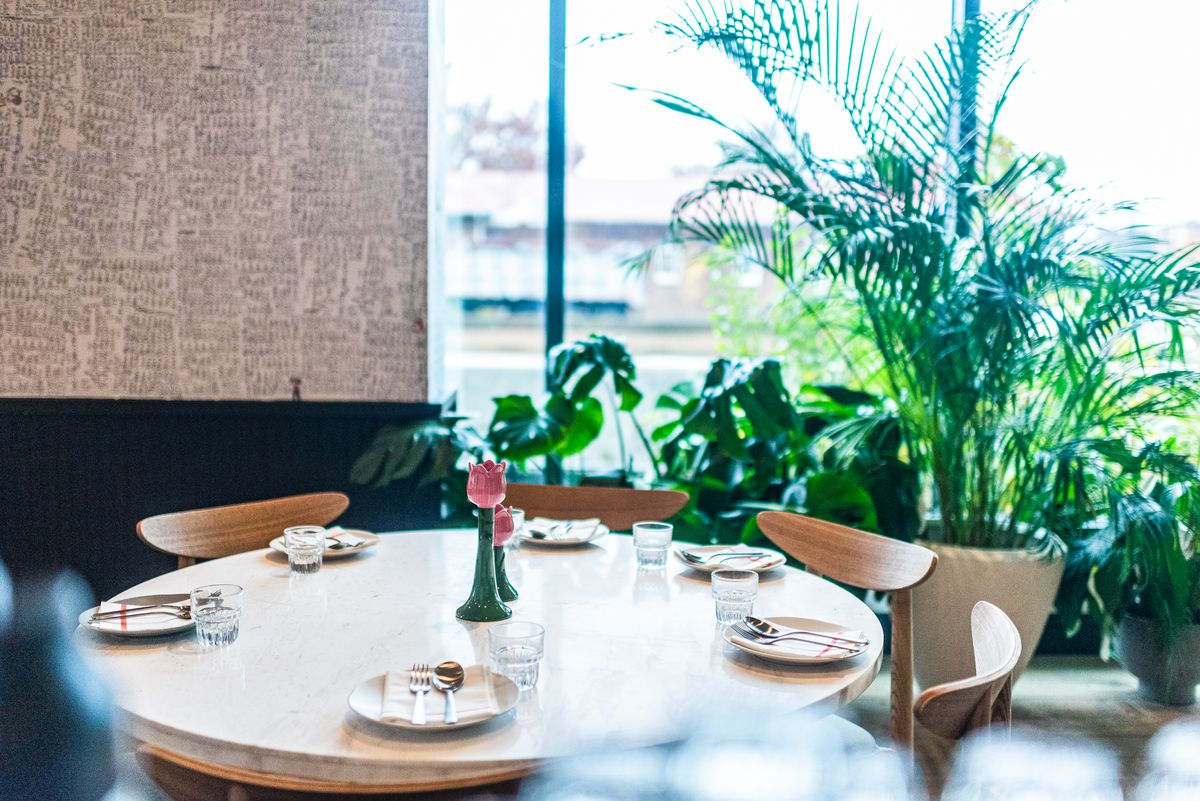 A white, circular table surrounded by green plants inside ABC Pony