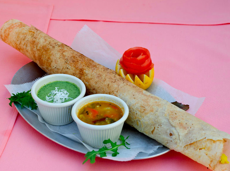 Dosa with sauces on a silver tray on a pale pink tablecloth