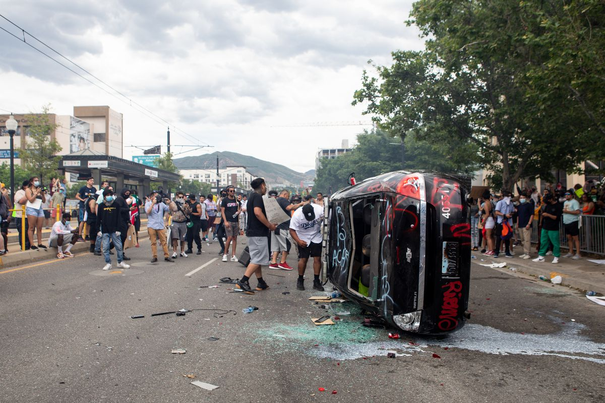 People stand beside a damaged police car as they protest police brutality in Salt Lake City on Saturday, May 30, 2020. Protesters joined others across the nation after George Floyd, a black man in Minnesota, died at the hands of police on Memorial Day.