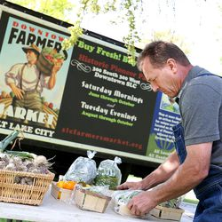 Kaysville farmer John Borski arranges vegetables and herbs from his gardens at a press conference announcing the start of the Farmer's Market in Pioneer Park in Salt Lake City on Thursday, June 11, 2015.