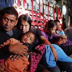 Frederick P. Caratao, his son Hizuka Caratao, wife Myrene Polillo and daughter Samantha Polillo ride in a military transport plane from Tacloban, Wednesday, Nov. 20, 2013, following a typhoon in the Philippines.