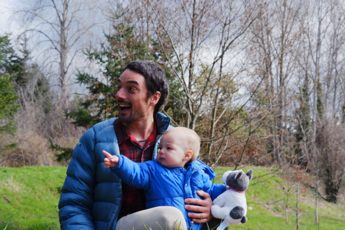 Eli Loomis holds his 1-year-old daughter, Alma, while she points at a dog at Squalicum Creek Park in Bellingham, Washington. Loomis has taken a renewed interest in his local parks now that he's unable to go on outdoor adventures.