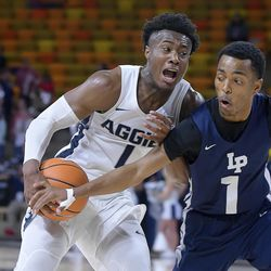 Utah State guard Koby McEwen drives to the basket as Life Pacific guard Chez Lister defends during an NCAA basketball game, Saturday, Dec. 16, 2017, in Logan, Utah. (Eli Lucero/Herald Journal via AP)