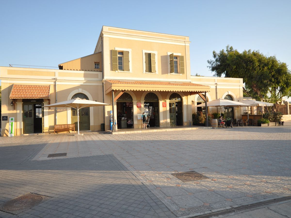 A train station (HaTachana) in Tel Aviv. The station is in a building which is tan with arched windows and doors.