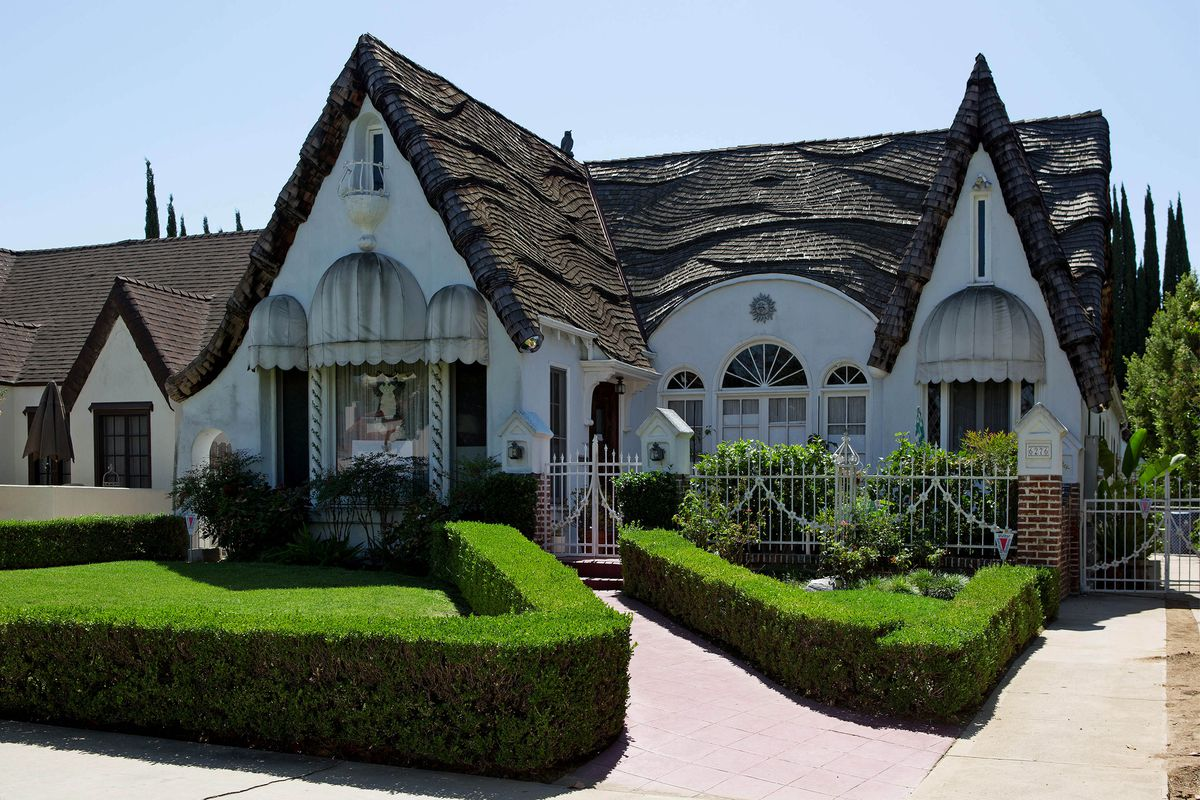 White Tudor-style home with dramatic dormers and neatly trimmed hedges in the front yard