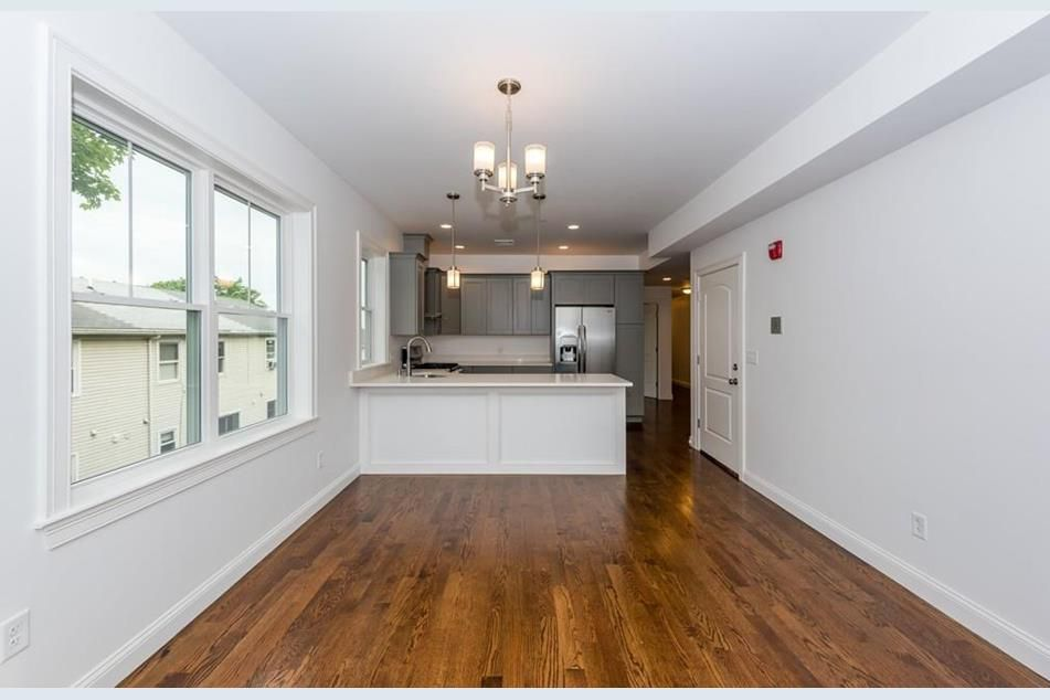 A long dining room area leading toward a kitchen, and there's no furniture.