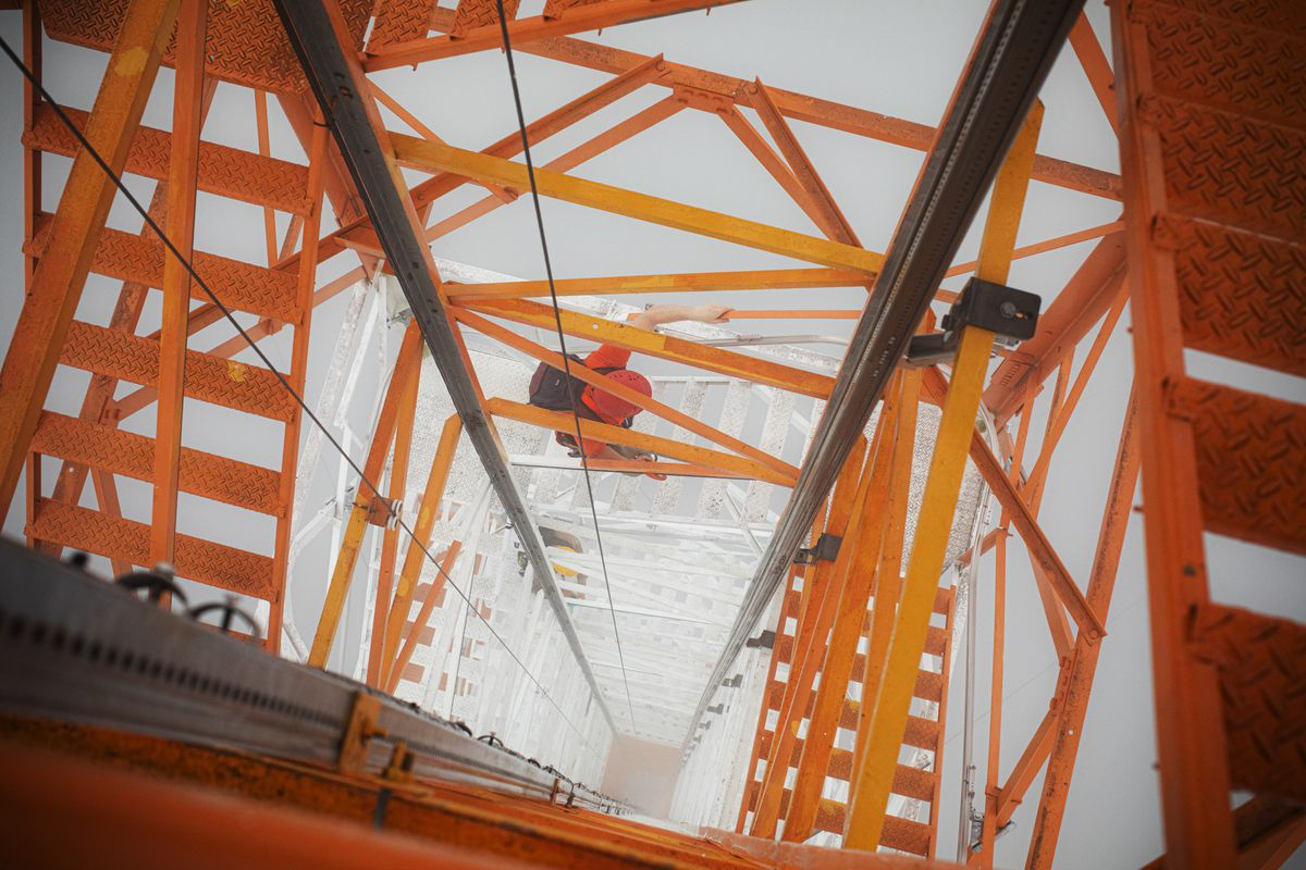 A top-down view of an orange metal network of bars and steps of the tower, shrouded in mist.