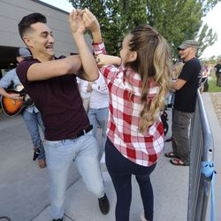 """Valen Hellyer and Kaitlyn Hellyer dance as others play music while waiting in line for """"American Idol"""" auditions outside of the Northwest Community Center in Salt Lake City on Thursday, Aug. 29, 2019."""