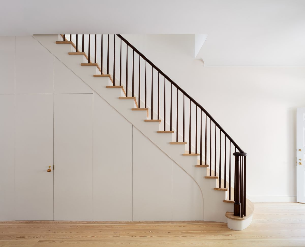 A staircase. The bannister is black and the stairs are wooden. The side of the staircase is painted white.
