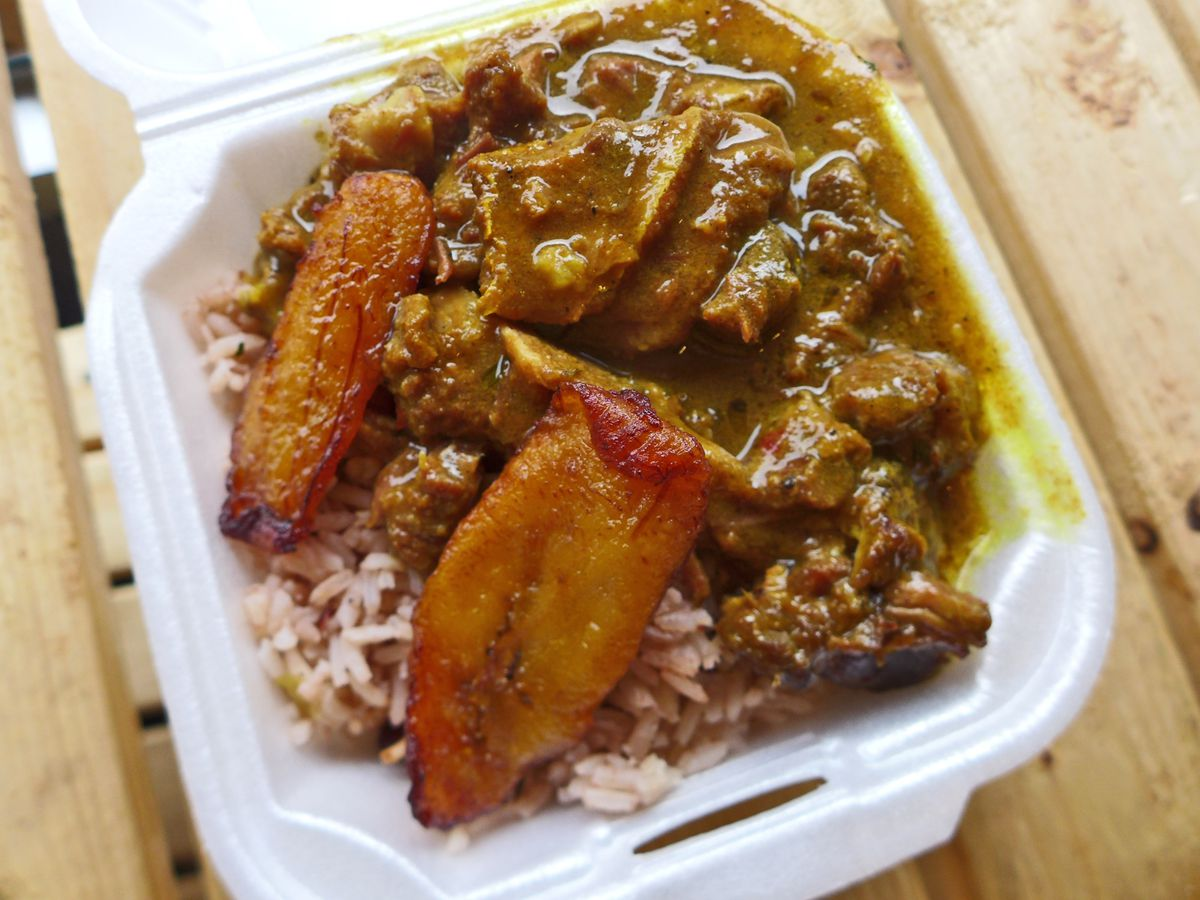 Goat curry over rice with fried plantains.