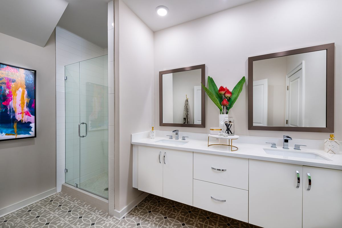 Bathroom with double vanity and glass shower.