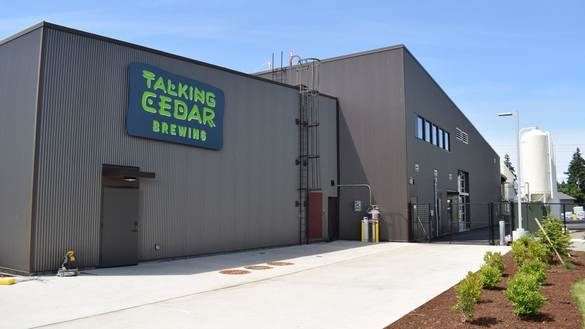 The gray exterior of Talking Cedar in Grand Mound, Washington, with the brewery's green lettering on the sign
