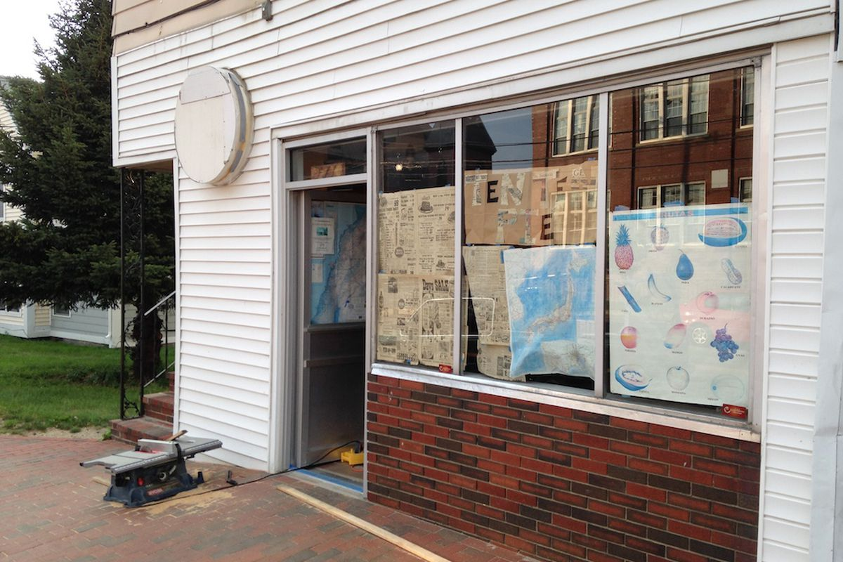 A temporary newspaper-cutout sign now hangs in the window.
