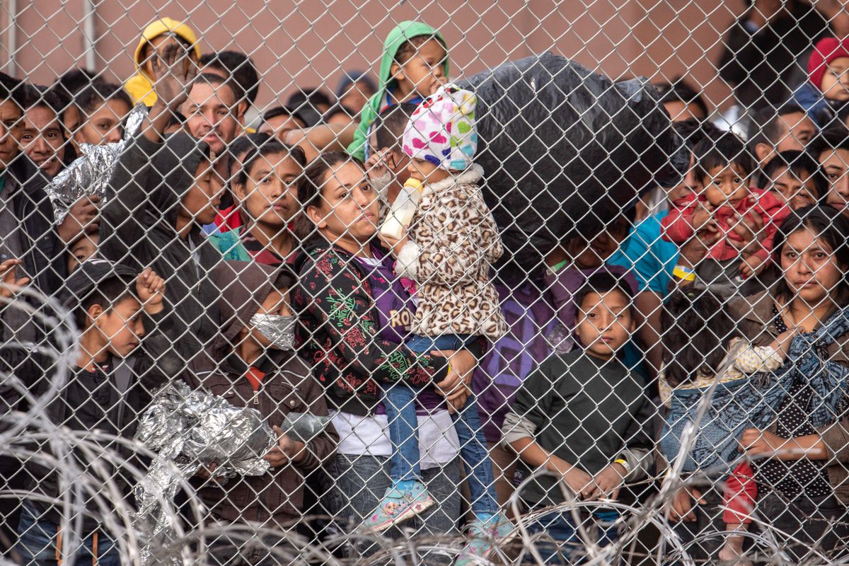 Migrant families behind a mesh fence.