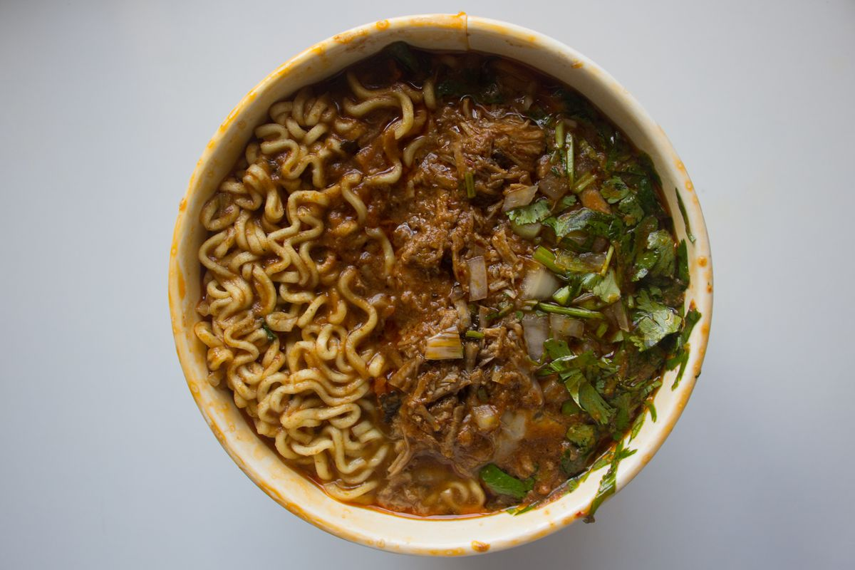 An above shot of a soupy ramen bowl with visible ramen noodles on the left, meat in the middle, and diced onions and cilantro on the right, on top of a white table