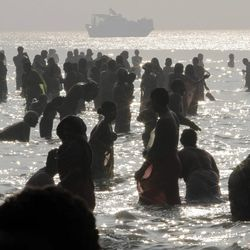 Hindu pilgrims take the annual holy dip on the auspicious 'Makar Sankranti' day at Gangasagar, the confluence of the Ganges River and the Bay of Bengal, about 140 kilometers (88 miles) south of Kolkata, India, Tuesday, Jan. 14, 2014. Devout Hindus believe that those who bathe in the Ganges on this day are absolved of their sins.