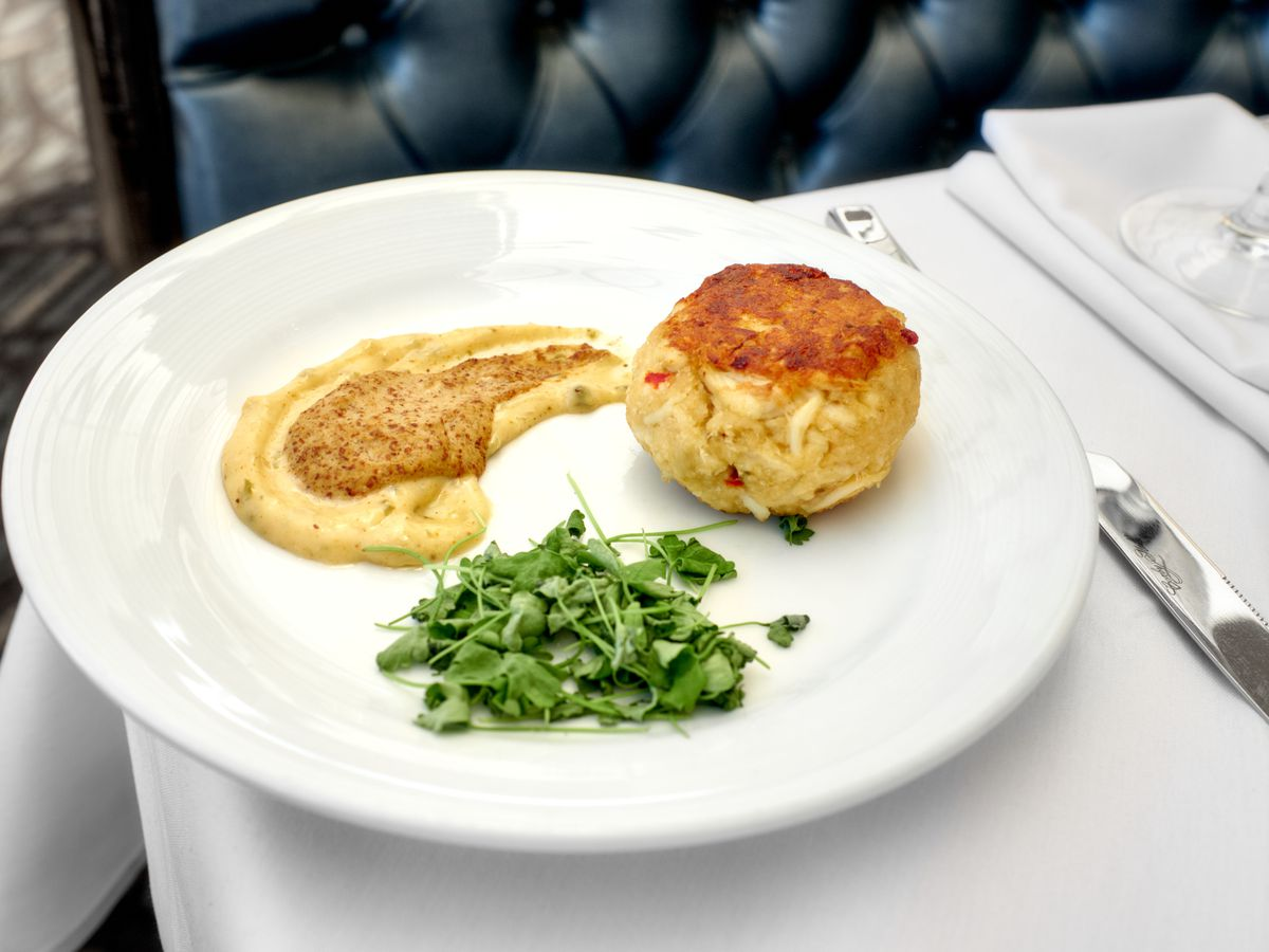 A crab cake on a plate with greens and aioli