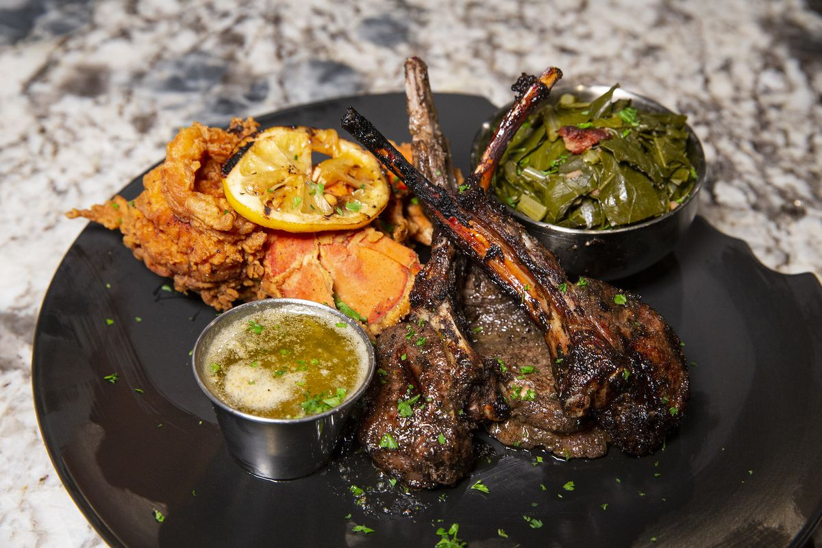 A trio of lamb chops on a plate with sides.