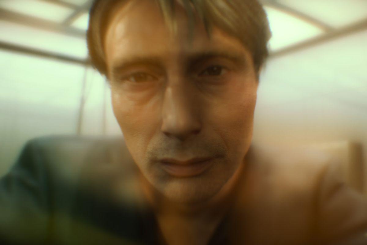a close-up of a sad-looking man (Mads Mikkelsen) seen through an orange haze in Death Stranding
