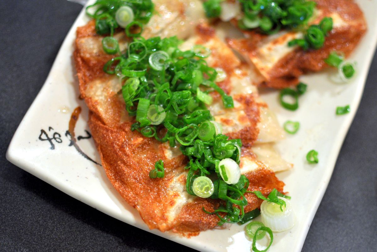 A raft of pan-fried Japanese dumplings with scallions.