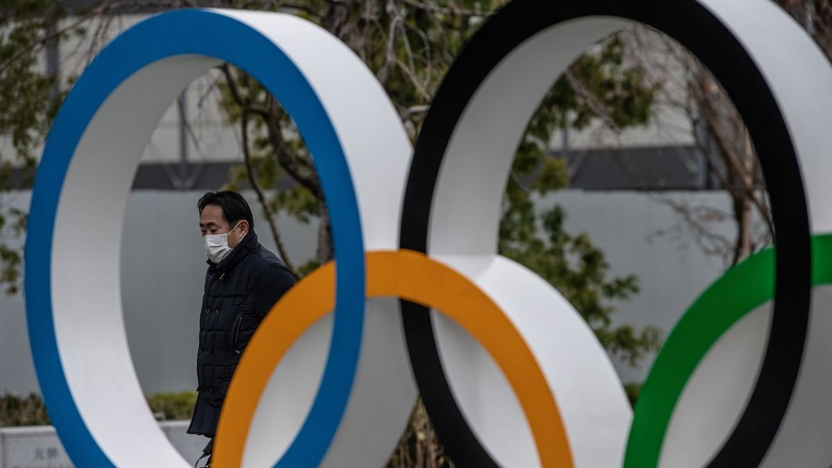 The picture is a closeup of a statue featuring the Olympic Rings in Tokyo. A man is pictured walking by wearing a mask to protect from the coronavirus With the Olympics just a few short weeks away, and dependent on a successful vaccine drive, the mood is pretty gloomy.