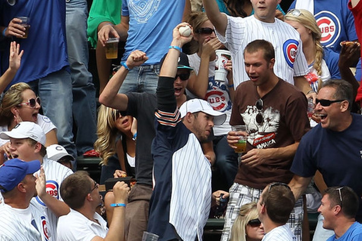 CHICAGO - SEPTEMBER 05: A fan in the left field bleachers holds up a home run ball hit by Aramis Ramirez of the Chicago Cubs against the New York Mets at Wrigley Field on September 5 2010 in Chicago Illinois. (Photo by Jonathan Daniel/Getty Images)
