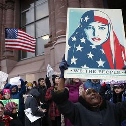 """Demonstrators chant against President Donald Trump's executive order temporarily banning immigrants from seven Muslim-majority countries from entering the U.S. and suspending the nation's refugee program Monday, Jan. 30, 2017, outside City Hall in Cincinnati. In addition, earlier in the day Mayor John Cranley declared Cincinnati a """"sanctuary city,"""" meaning city will not enforce federal immigration laws against people who are here illegally, in keeping with current policy. (AP Photo/John Minchillo)"""