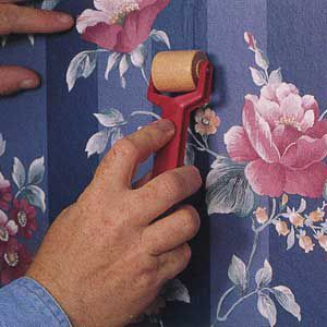 <p>SMOOTH OUT THE paper using a wooden seam roller, then wipe off any excess adhesive with a damp sponge.</p>