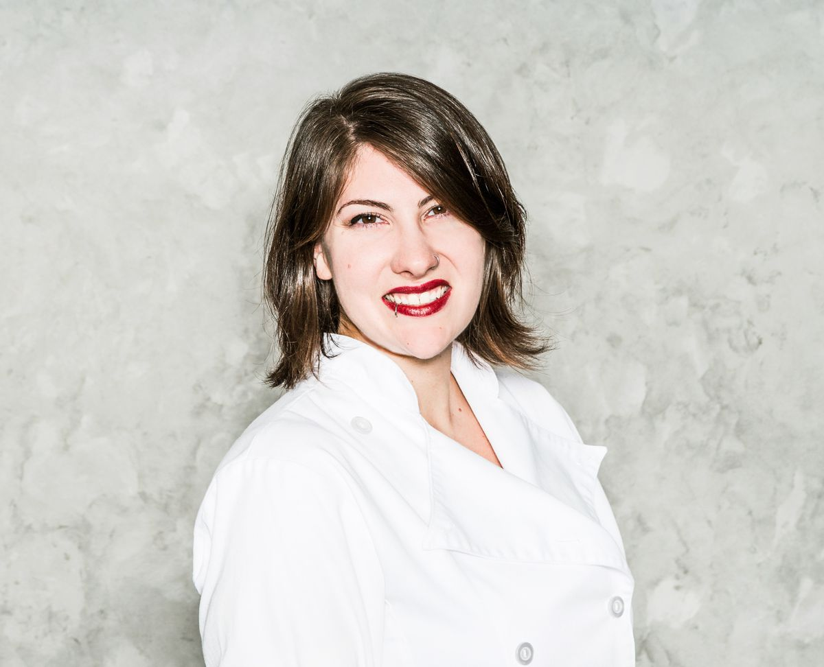 A woman in a white chef's coat with mid-length brown hair