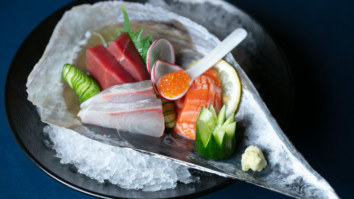 Sashimi at Omakase, served in a silver oyster shell shaped vessel with a spoon of roe.