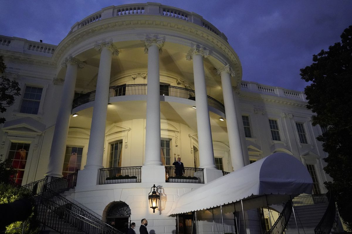 President Donald Trump salutes from a White House balcony on Monday, Oct. 5, 2020, in Washington, after leaving Walter Reed National Military Medical Center, in Bethesda, Md.