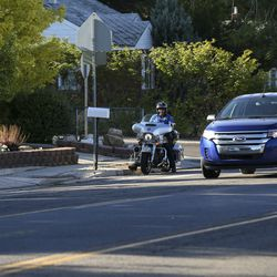 A Unified police officer talks with crossing guard Newell Evans, left, on 1300 East near Millcreek Elementary School in Millcreek on Monday, Aug. 19, 2019. The officer patrolled the area briefly Monday morning as students were arriving for their first day of school. Twice, within a minute of pulling out his radar gun, the officer pulled a motorist over.