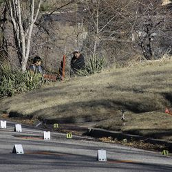 Neighbors watch as law enforcement officers and crime scene investigators continue to work at the scene of an overnight shooting at a home in Ogden Thursday, Jan. 5, 2012.  Six officers, some from the Weber-Morgan Narcotics Strike Force were shot while serving a warrant at 3268 Jackson Ave.