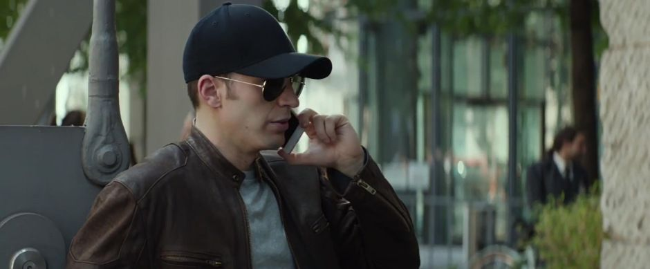Captain America disguised in a brown leather jacket, aviators, and a logo-less black baseball cap
