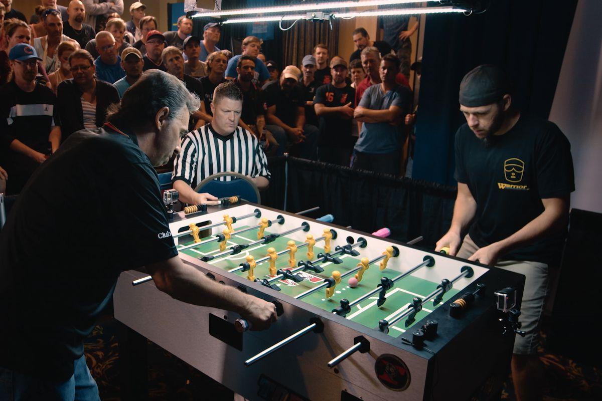 "Spectators watch Tony Spredeman (right) compete against Todd Loffredo in ""Foosballers."""