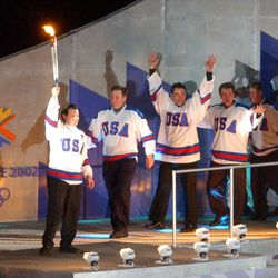 The 1980 U.S. hockey team lights the cauldron during the Salt Lake 2002 Winter Games opening ceremony at the University of Utah's Rice-Eccles Stadium on Friday, Feb. 8, 2002.