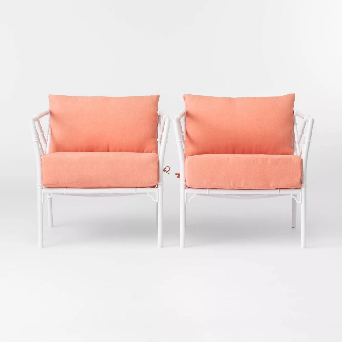 Chair with coral cushions and white frame.